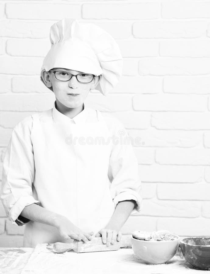 年轻白色制服和帽子的男孩逗人喜爱的厨师厨师在与玻璃的被弄脏的面孔面粉烹调在与滚针的桌上的 免版税库存照片