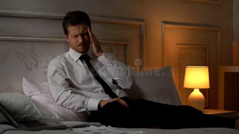 年轻疲乏的商人痛苦偏头痛,专业烧坏,工作狂 图库摄影