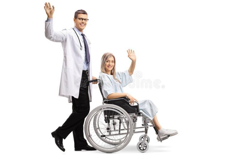 年轻男性医生和一名女性患者轮椅挥动的 库存图片