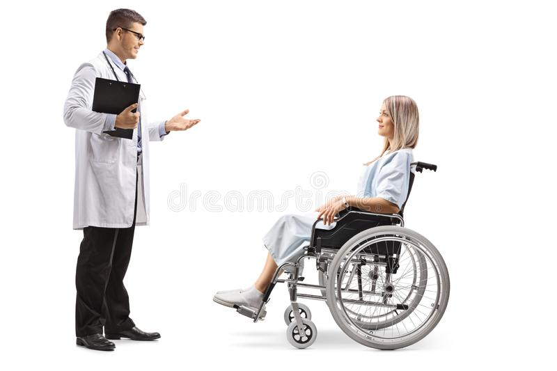 年轻男性医生谈话与轮椅的一年轻女人 库存图片
