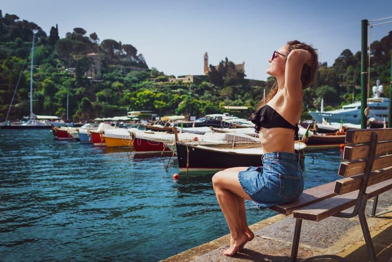 年轻赤足妇女坐长凳在小游艇船坞 免版税库存照片