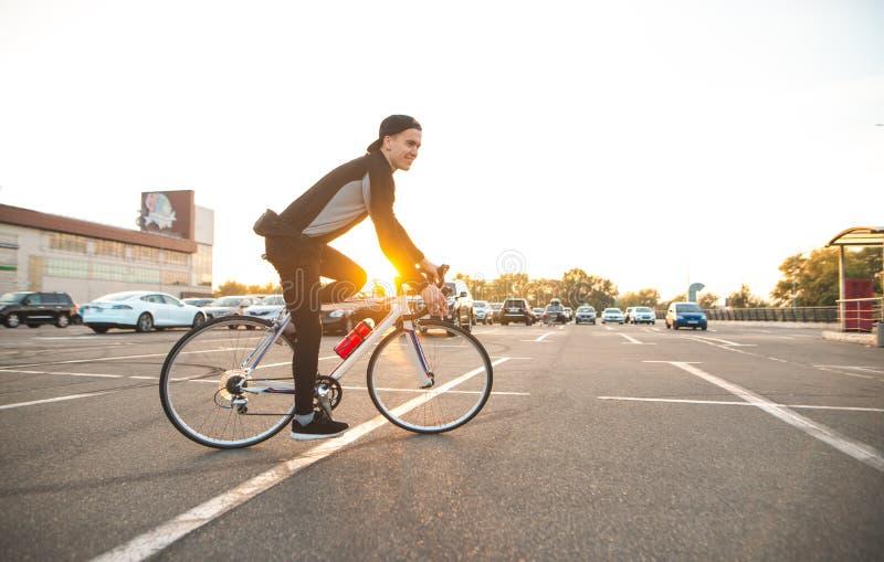年轻车手在日落和神色的背景骑一辆自行车在城市在照相机 免版税图库摄影
