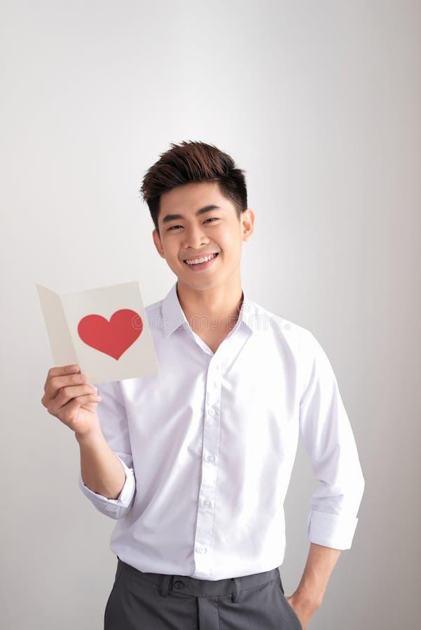 年轻英俊的亚裔人在白色背景读与心形的贺卡 库存照片