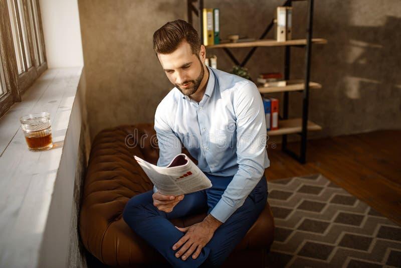 年轻英俊的商人读书学报在他自己的办公室 他坐在窗口和读的学报 杯威士忌酒立场 图库摄影