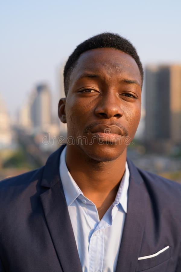 年轻英俊的非洲商人的面孔反对城市的看法的 图库摄影