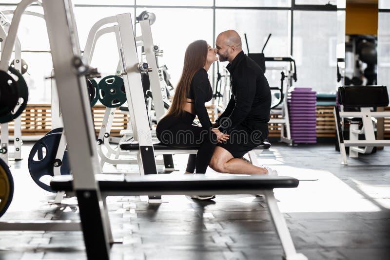 年轻苗条俏丽的女孩和残酷运动人亲吻一起坐在现代健身房的体育长凳 免版税库存图片