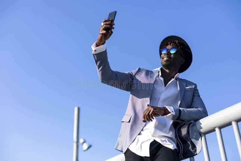 年轻非洲倾斜在金属篱芭的黑人佩带的帽子和太阳镜低角度视图放松,当采取selfie时 图库摄影