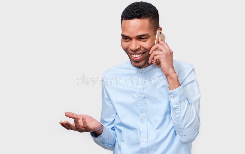 年轻非裔美国人的人谈话在手机与他的朋友,看快乐和愉快,摆在白色演播室背景 库存图片