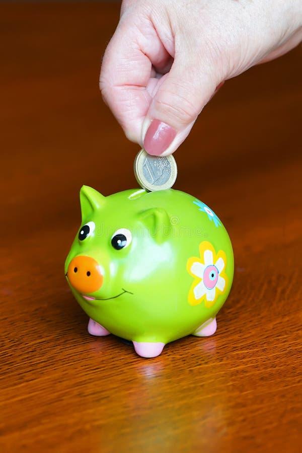 年长妇女存金钱 放硬币的资深妇女手特写镜头入存钱罐 库存图片