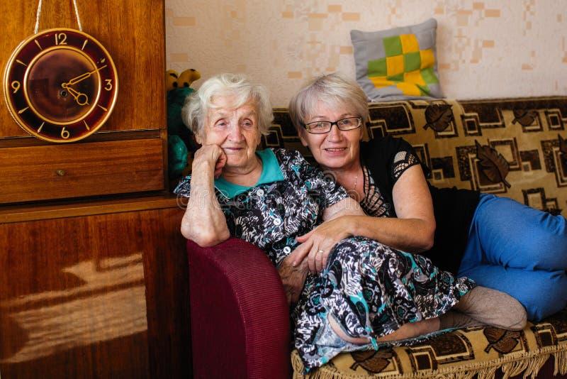 年长妇女在他的家坐有成人女儿的长沙发 家庭 免版税库存照片
