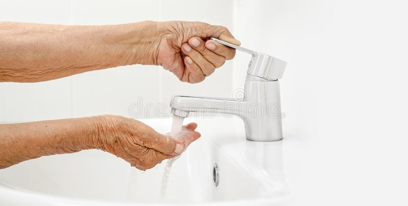 年长妇女在卫生间里洗手 免版税库存图片
