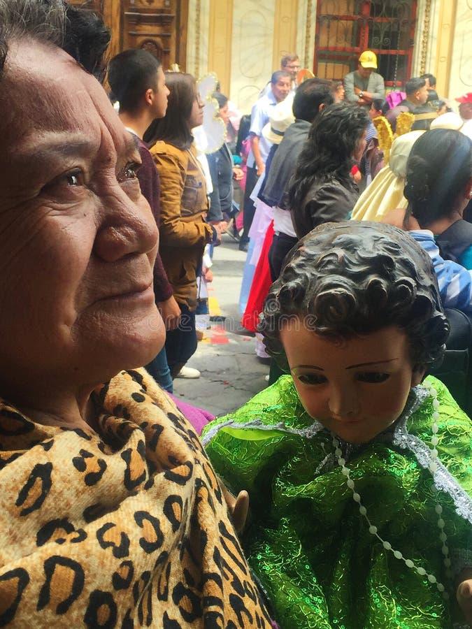年长妇女抱着小耶稣在Pase del NiA±oo Christmas游行期间在昆卡省厄瓜多尔 免版税库存照片