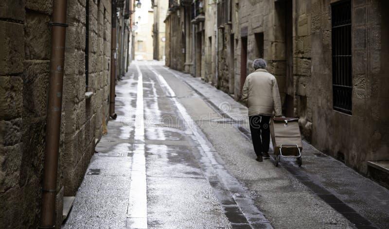 年长妇女走的街道 免版税图库摄影
