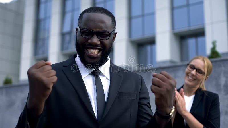 庆祝合同签字的快乐的商人,表现出幸福情感 免版税库存照片