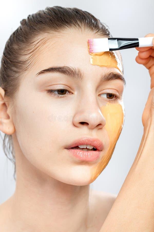 应用与一把刷子的黄色化妆面具的过程在年轻棕色毛发的女孩的面孔 库存图片