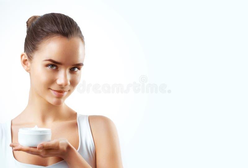 应用一些奶油的美丽的妇女画象于她的护肤的面孔 免版税图库摄影