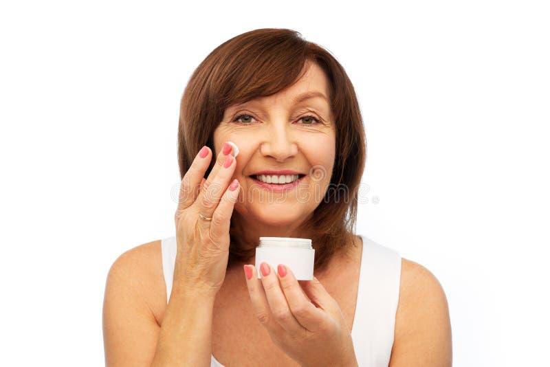 应用奶油的微笑的资深妇女于她的面孔 免版税库存图片