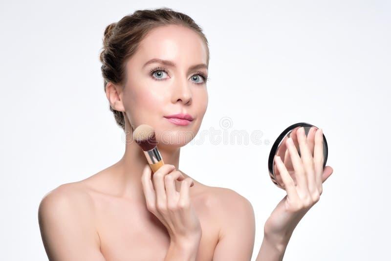 应用完善的神色的欧洲俏丽的妇女皮肤粉末 免版税库存照片