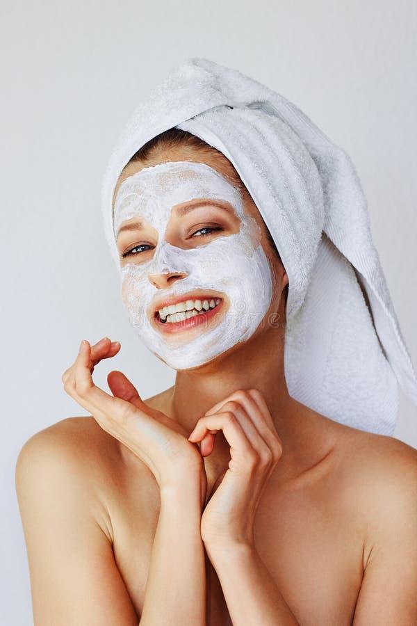 应用在她的面孔的美丽的年轻女人面膜 皮肤护理和治疗、温泉、自然美人和整容术概念 库存照片