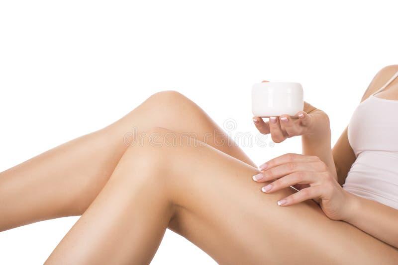 应用在腿上的美丽的少妇奶油,当在家时坐床 去除概念的皮肤护理和头发 库存照片
