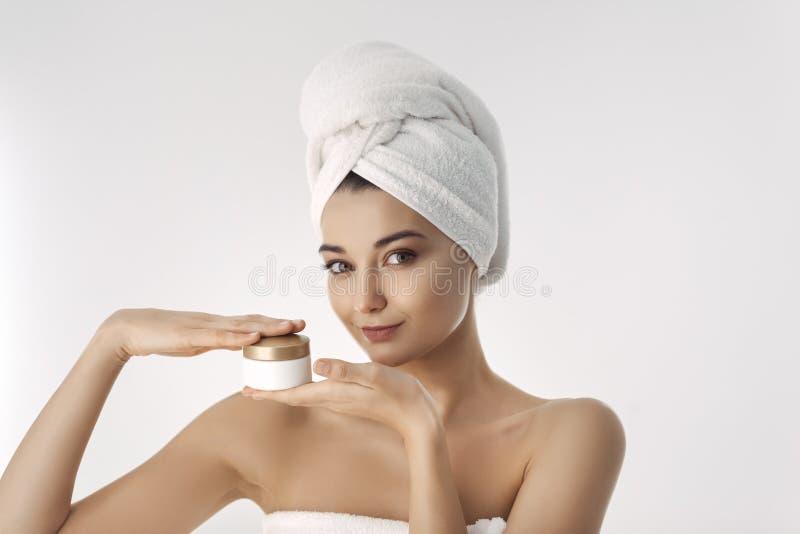 应用关心皮肤透明油漆 有拿着面霜的自然面孔秀丽的妇女 免版税库存图片
