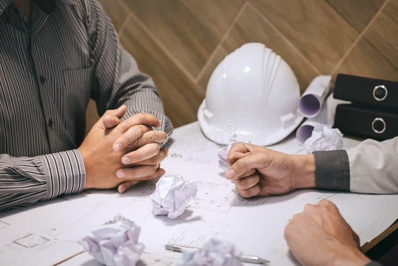 建设工程队或建筑师伙伴谈论图纸,当检查关于画和速写时的信息 免版税图库摄影