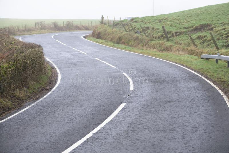弯曲的国家空的农村路空白线路和树篱 图库摄影