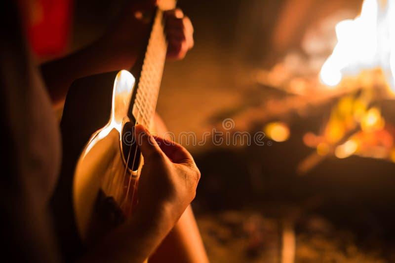 弹吉他的一位女性音乐家外面,坐在火旁边 放松 免版税图库摄影