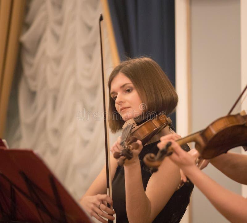 弹小提琴的美丽的年轻女人在音乐厅里 免版税库存照片