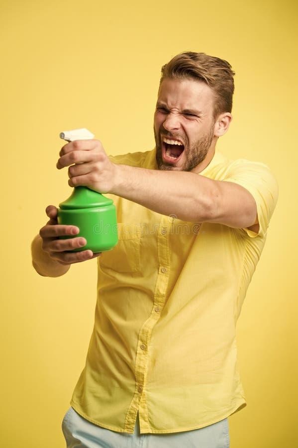 强壮男子的作为枪黄色背景的举行塑料浪花瓶 有喷水的人在手中假装射击攻击 库存照片