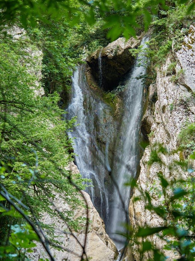 强有力的瀑布从在春天山河的峭壁落 图库摄影