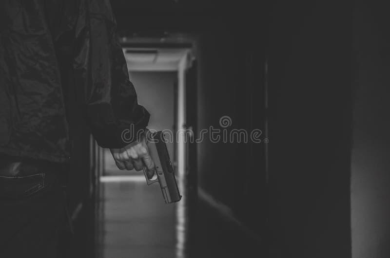 强盗或匪徒,窃贼藏品枪在手中边他准备好射击,谋杀,罪行 免版税图库摄影