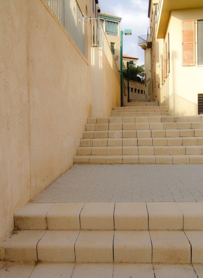Żółta grodzka schodek ścieżka przyglądająca w górę ściany i budynków mieszkalnych pośrodku, pokazywać małego przejście i latarnie zdjęcia royalty free