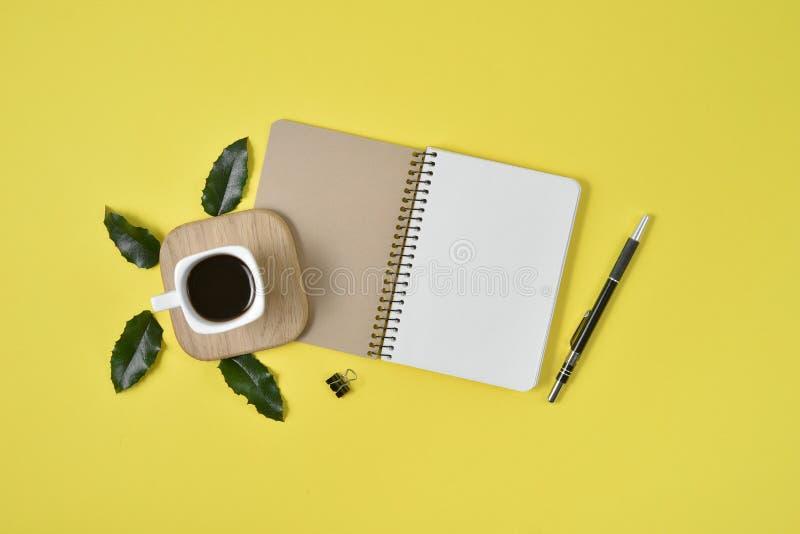 Żółty biurowego biurka stół z pustym notatnikiem, zielonym liściem, piórem, dostawami i filiżanką, Mieszkanie nieatutowy, odgórny fotografia stock