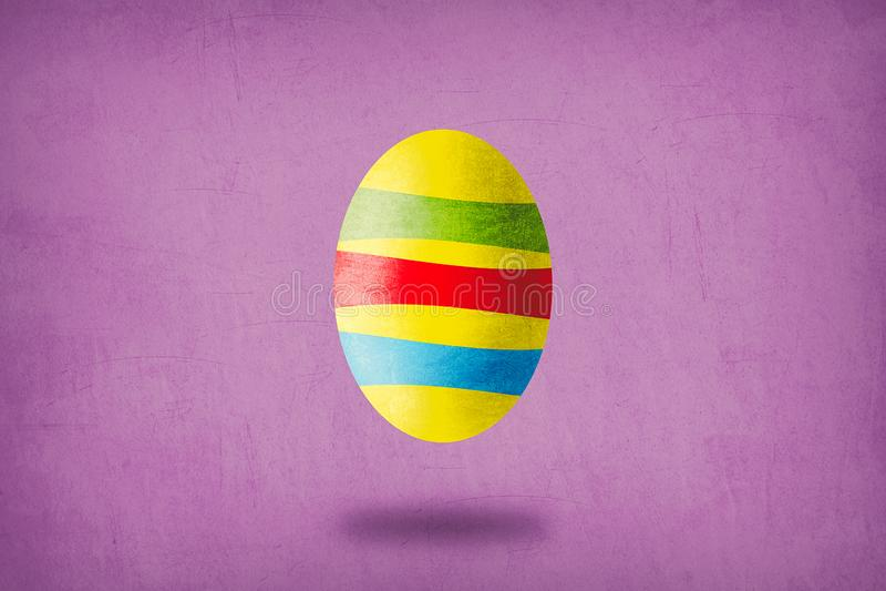 Żółty jajko z zielenią, czerwienią i błękitnymi lampasami na purpurowym tle, zdjęcie stock