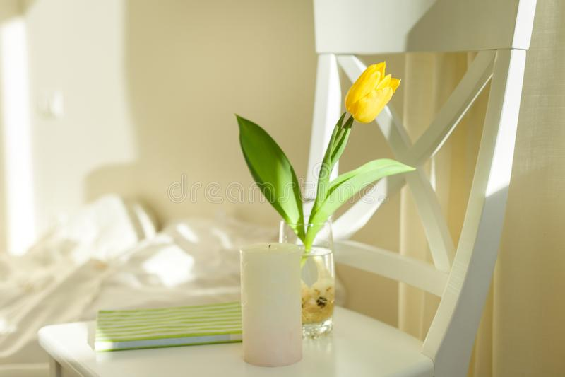 Żółty tulipanowy kwiat w szkle z wodą na białym krześle w sypialni wnętrzu, pogodny wiosna dzień fotografia stock