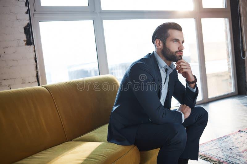 引起想法 确信和英俊的年轻商人考虑事务,当坐在他的时的沙发 免版税库存图片