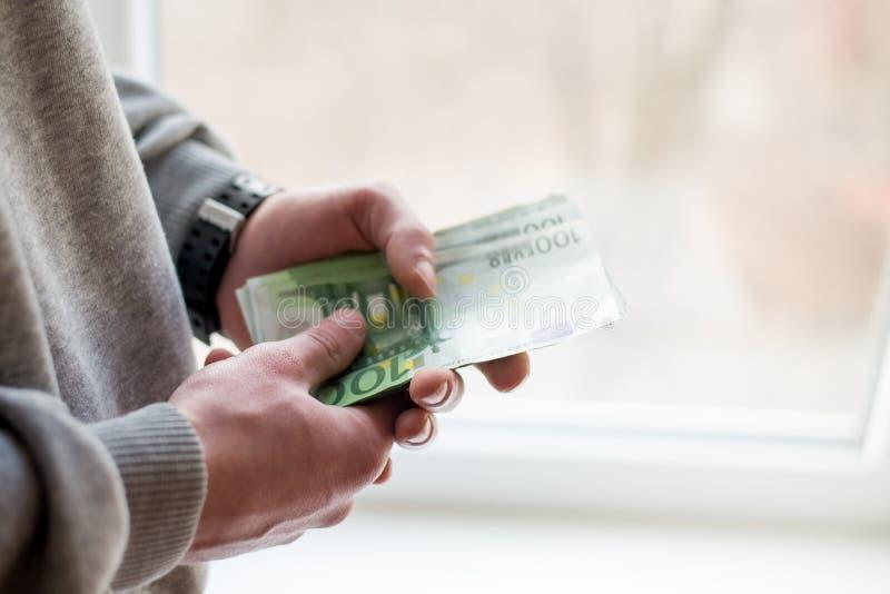 开户欧洲欧元五重点一百货币附注绳索 纸欧元钞票在人手上 人给贿款 免版税库存照片