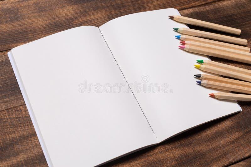 开放笔记本的顶视图图象有空白页的在咖啡在木桌上的旁边 为大模型准备 免版税库存照片