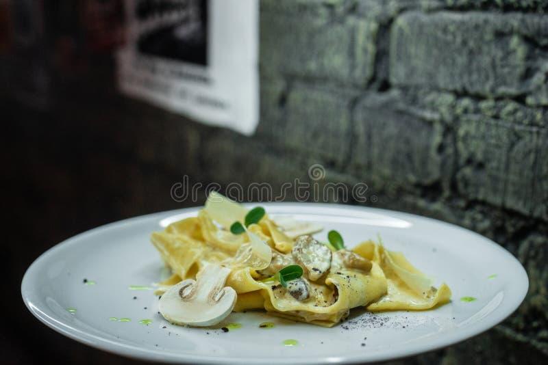 开胃热的面条快餐用在一个灰色砖墙的背景的乳脂状的蘑菇调味汁在酒吧的 在猪纵向时间白色的背景滑稽的几内亚午餐 免版税库存图片