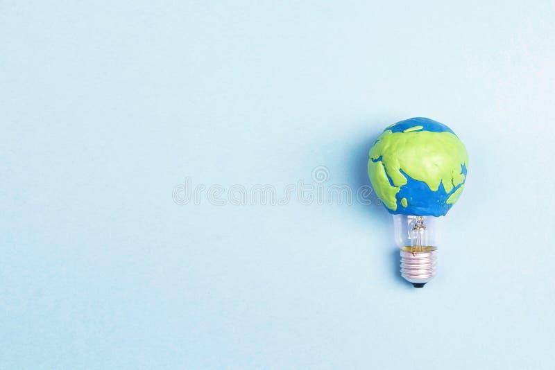 Żarówka z plasteliny ziemi planety modelem na błękitnym tle z przestrzenią dla teksta zdjęcie stock