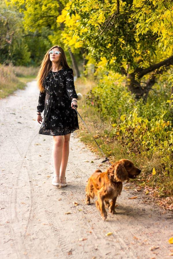 Żartuje dziewczyny w smokingowym bieg z psem w wsi przy susnset fotografia stock