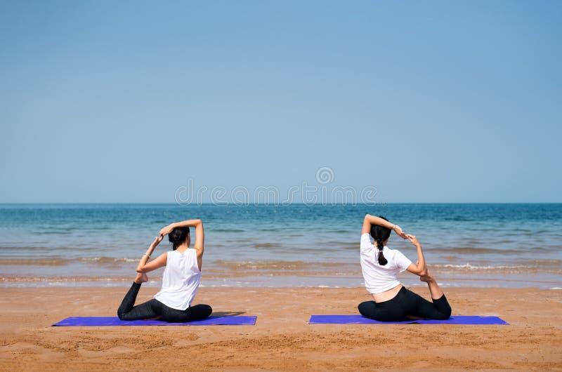 Żeńscy przyjaciele ćwiczy joga na plaży zdjęcie stock