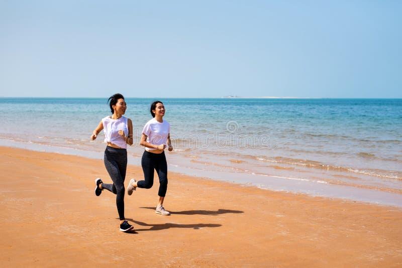 Żeńscy przyjaciele biega na plaży zdjęcia stock