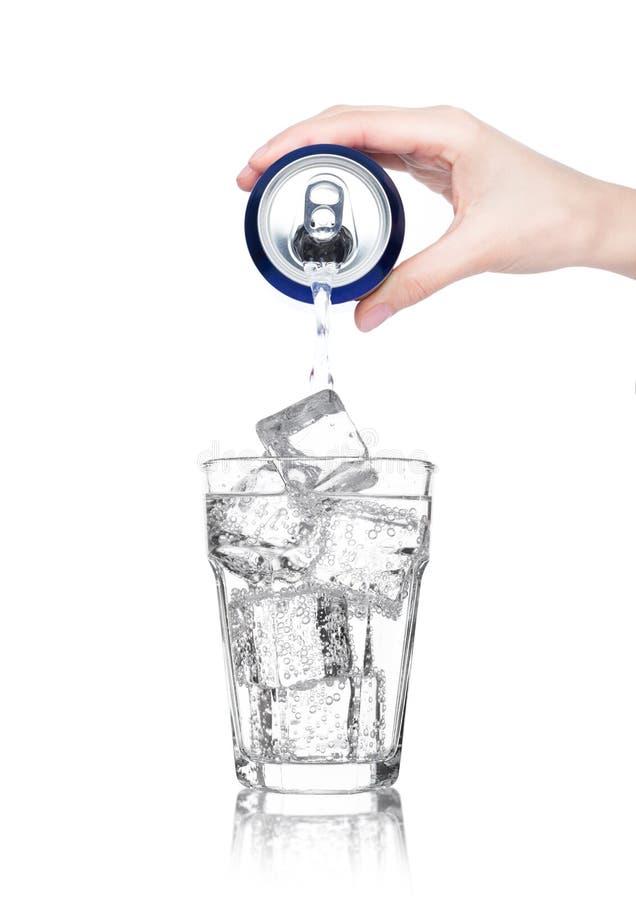 Żeńska ręka nalewa iskrzastą wodę od puszki cyny zdjęcie royalty free