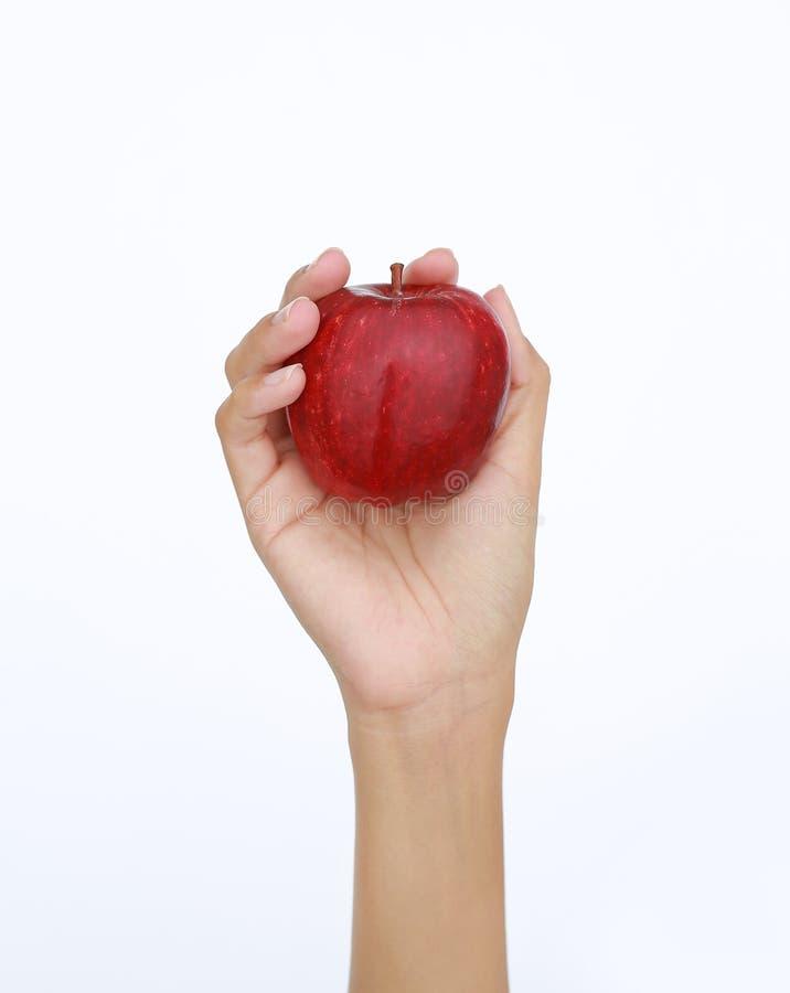Żeńska ręka trzyma czerwonego jabłka na białym tle i pokazuje fotografia stock