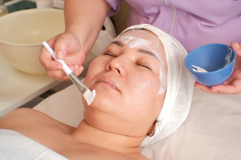 Żeński beautician stosuje czyści maskę na twarzy z muśnięciem w zdroju salonie Zakończenie Kosmetyczna procedura dla twarzowego obrazy stock
