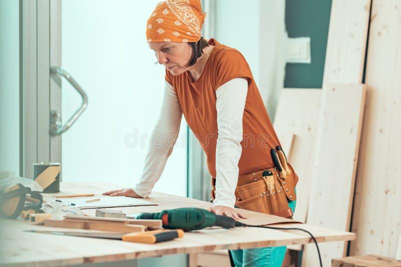 Żeński cieśla z bandanna pozuje w woodwork warsztacie fotografia stock