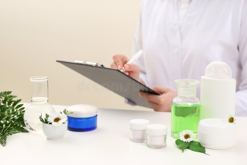Żeński dermatolog robi badaniu dla nowego skóry opieki produktu przy stołem zdjęcia stock