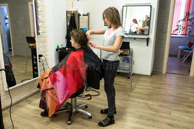Żeński fryzjer ciie włosy kobieta klient w fryzjerstwo salonie wśród luster na miarowym dniu powszednim, fotografia royalty free